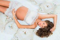 Bella ragazza incinta in pizzo bianco sul letto, vista superiore Fotografia Stock