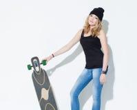 Bella ragazza intelligente alla moda in jeans, maglietta nera e cappello che posano con un longboard fresco nelle mani Fotografia Stock Libera da Diritti