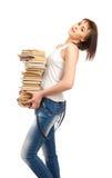 Bella ragazza che tiene una pila di libri Immagini Stock