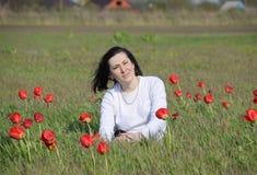 Bella ragazza leggiadramente in un campo fra i fiori dei tulipani Ritratto di una ragazza su un fondo dei fiori rossi e di una f  Fotografie Stock