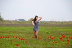 Bella ragazza leggiadramente in un campo fra i fiori dei tulipani Ritratto di una ragazza su un fondo dei fiori rossi e di una f  Immagine Stock