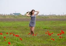 Bella ragazza leggiadramente in un campo fra i fiori dei tulipani Ritratto di una ragazza su un fondo dei fiori rossi e di una f  Fotografia Stock Libera da Diritti