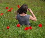 Bella ragazza leggiadramente in un campo fra i fiori dei tulipani Ritratto di una ragazza su un fondo dei fiori rossi e di una f  Immagini Stock Libere da Diritti