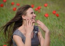 Bella ragazza leggiadramente in un campo fra i fiori dei tulipani Ritratto di una ragazza su un fondo dei fiori rossi e di una f  Fotografie Stock Libere da Diritti