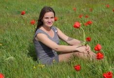 Bella ragazza leggiadramente in un campo fra i fiori dei tulipani Ritratto di una ragazza su un fondo dei fiori rossi e di una f  Fotografia Stock