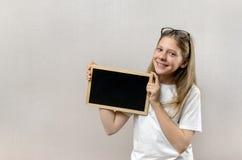 Bella ragazza maligna con i vetri che tengono un segno dentro le sue mani Copia-spazio immagine stock
