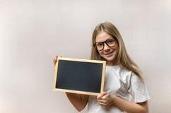 Bella ragazza maligna con i vetri che tengono un segno dentro le sue mani Copia-spazio immagini stock