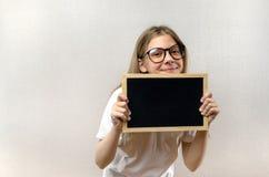 Bella ragazza maligna con i vetri che tengono un segno dentro le sue mani Copia-spazio fotografia stock