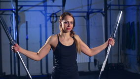 Bella ragazza muscolare in cima nera e ghette nere che fanno un esercizio con un bilanciere nella palestra in un industriale video d archivio