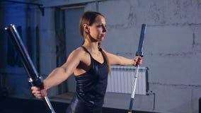 Bella ragazza muscolare in cima nera e ghette nere che fanno un esercizio con un bilanciere nella palestra in un industriale archivi video