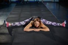 Bella ragazza muscolare in ghette grige che fanno allungamento Mette in mostra la palestra nello stile industriale Fotografie Stock Libere da Diritti