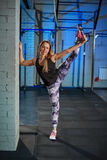 Bella ragazza muscolare in ghette grige che fanno allungamento Mette in mostra la palestra nello stile industriale Immagine Stock