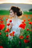 Bella ragazza nei campi del papavero al tramonto fotografia stock