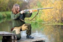 Bella ragazza nel cacciatore del cammuffamento con il fucile da caccia Fotografia Stock