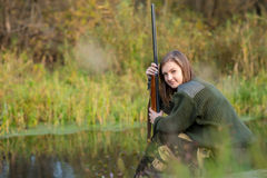 Bella ragazza nel cacciatore del cammuffamento con il fucile da caccia Fotografia Stock Libera da Diritti