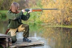 Bella ragazza nel cacciatore del cammuffamento con il fucile da caccia Immagini Stock Libere da Diritti