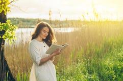Bella ragazza nel campo che legge un libro La ragazza che si siede su un'erba, leggente un libro Resto e lettura immagini stock libere da diritti