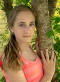 Bella ragazza nel giardino vicino all'albero, Fotografia Stock