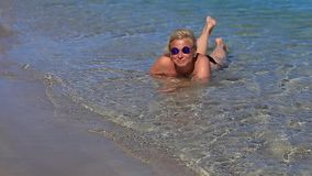 Bella ragazza nel mare sulla sabbia video d archivio
