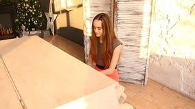 Bella ragazza nel sittyng e nel gioco del vestito del pianoforte a coda video d archivio