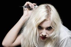 Bella ragazza nell'immagine dell'infermiere diabolico con la siringa a disposizione che fa un colpo Immagini Stock