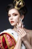 Bella ragazza nell'immagine della regina nel manto con una corona sulla testa e sui chiodi lunghi Fronte di bellezza fotografia stock libera da diritti