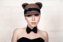 Bella ragazza nell'immagine di un gatto, ritratto dello studio Immagine Stock