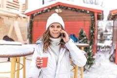 Bella ragazza nell'inverno in città su una festa, chiamate sul telefono Sorridere felice in sue mani una tazza di caffè con fotografia stock