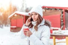 Bella ragazza nell'inverno nella città, chiamate sul telefono, in un cappello ed in un rivestimento bianchi In sua mano tiene una fotografia stock