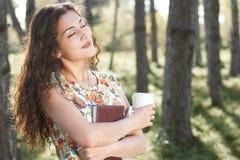 Bella ragazza nella foresta, nella luce solare luminosa intorno, nell'erba verde e negli alberi fotografie stock libere da diritti