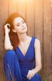 Bella ragazza nella seduta blu del vestito Fotografia Stock Libera da Diritti
