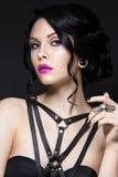 Bella ragazza nello stile gotico con gli accessori di cuoio ed il trucco luminoso Fronte di bellezza Fotografia Stock