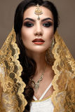 Bella ragazza nello stile indiano con una sciarpa sulla sua testa Modello con un trucco creativo e luminoso Immagini Stock