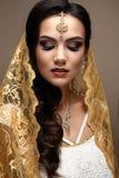 Bella ragazza nello stile indiano con una sciarpa sulla sua testa Modello con un trucco creativo e luminoso fotografie stock libere da diritti