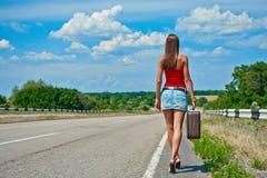Bella ragazza o donna in mini con la valigia che fa auto-stop lungo una strada Immagini Stock