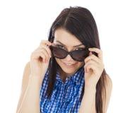 Bella ragazza in occhiali da sole che esaminano la macchina fotografica e sorridere Fotografia Stock