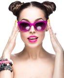 Bella ragazza in occhiali da sole rosa con trucco luminoso ed i chiodi variopinti Fronte di bellezza fotografie stock