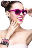 Bella ragazza in occhiali da sole rosa con trucco luminoso ed i chiodi variopinti Fronte di bellezza immagini stock
