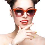 Bella ragazza in occhiali da sole rossi con trucco luminoso ed i chiodi variopinti Fronte di bellezza immagini stock