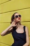 Bella ragazza in occhiali da sole vicino alla parete gialla Fotografie Stock Libere da Diritti
