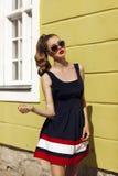 Bella ragazza in occhiali da sole vicino alla parete gialla Fotografie Stock