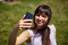 Bella ragazza orientale di aspetto che fa selfie su uno smartphone Immagine Stock