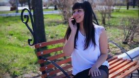 Bella ragazza orientale in una blusa bianca che si siede in un parco su un banco, sorridere e sugli inizio parlante sul telefono, stock footage
