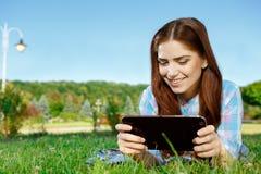 Bella ragazza in parco con il touchpad Fotografia Stock