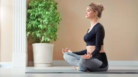 Bella ragazza piacevole sorridente che gode della meditazione nella posa del loto che si rilassa alla foto a figura intera dello  stock footage