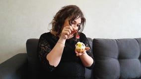 Bella ragazza piena con le torte sul sofà archivi video