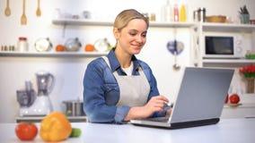 Bella ragazza positiva che cerca cucinando le punte in Internet, principiante in cucina fotografie stock libere da diritti