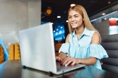 Bella ragazza positiva che lavora ad un computer portatile, comperante sopra la I immagine stock libera da diritti