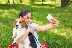 Bella ragazza presa le immagini del suo auto con il cane Instagram fotografia stock