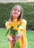 Bella ragazza preteen sorridente che dà mazzo dei tulipani di giallo della molla che esaminano macchina fotografica immagini stock
